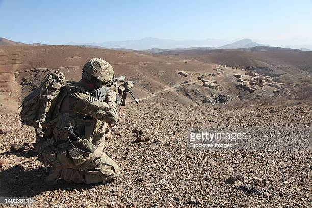 u.s. army soldier provides security for infantry patrolling through dandarh village, afghanistan. - afghanistan stock pictures, royalty-free photos & images