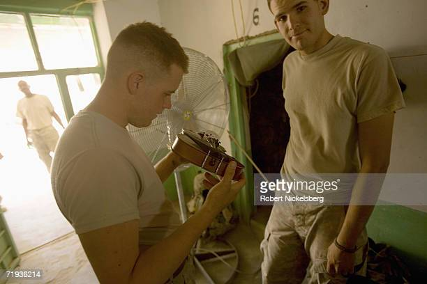 Army soldier, right, shows a fellow soldier a violin sent to him by his grandmother at Forward Operating Base Mizan in Zabul Province, Afghanistan...