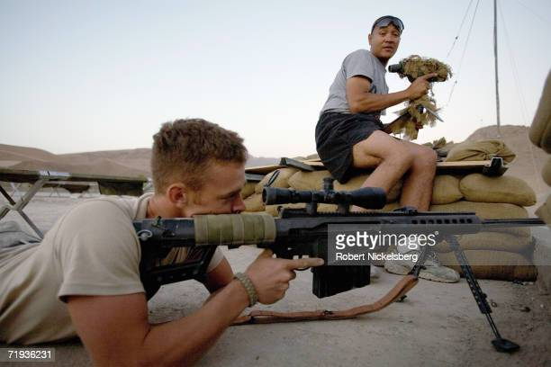 Army soldier, right, uses a spotting scope to help a soldier sight in a Barrett 50 caliber rifle on a group of approaching Taliban outside the...