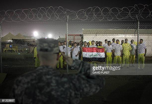 Army soldier salutes Iraqi detainees holding an Iraqi flag and singing the Iraqi national anthem after the soldier prompted them to do so inside the...