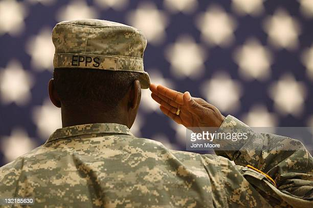 S Army soldier salutes the flag during the national anthem at a welcome home ceremony for troops returning from Iraq on November 10 2011 in Fort...