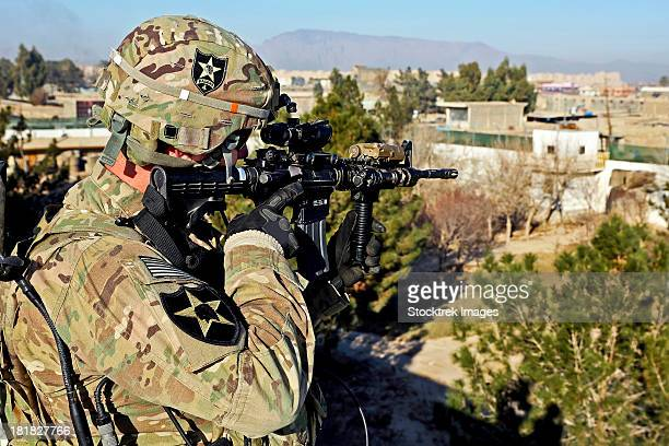 U.S. Army soldier scans for security threats from the rooftop.