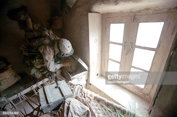 A US Army soldier searches a Pashtun village home for weapons and hideaways