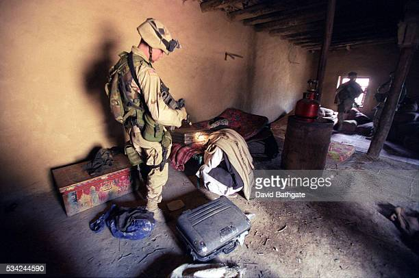 A US Army soldier searches a Pashtun village home on the southeast border with Pakistan