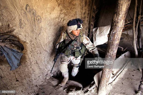 A US Army soldier searches a Pashtun village house on the southern border with Pakistan
