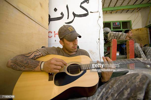Army soldier, Sgt. Florian Barrie, from C Company, 1-4 Infantry Regiment, plays an acoustic guitar at the Forward Operating Base Mizan in Zabul...