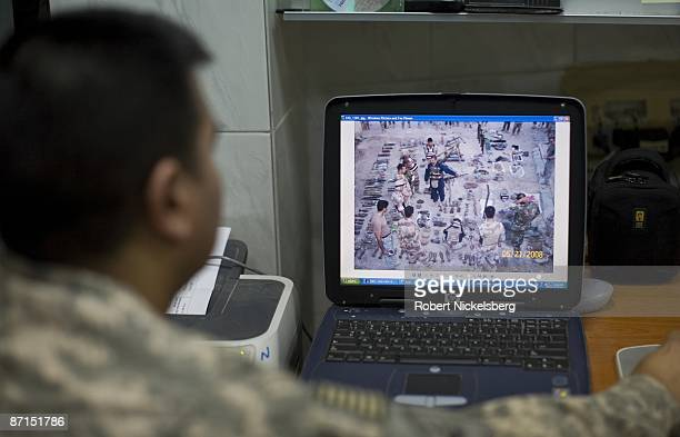 Army soldier shows a photo on his computer of Iraqi Army soldiers and a Shiite militia weapons cache captured two days ago in Sadr City the 25...
