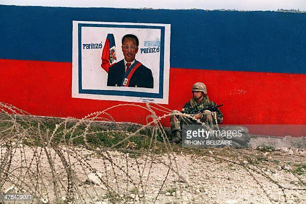 A US army soldier sits near a poster depicting Haitian President JeanBertrand Aristide on December 13 1994 in PortauPrince Thousands of US soldiers...