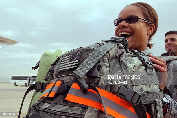 A US army soldier smiles as she prepares to fly out of Iraq and home from the alAsad Air Base west the capital Baghdad on November 1 2011 The massive...