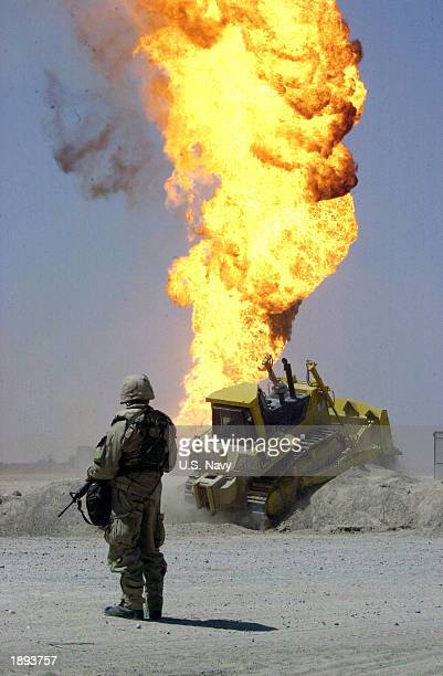 S Army soldier stands guard duty near a burning oil well April 2 2003 in the Rumaylah Oil Fields in Southern Iraq Coalition forces have successfully...