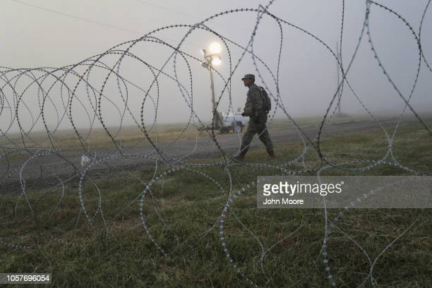 S Army soldier stands on guard duty near the USMexico border on November 5 2018 in Donna Texas Troops had set up razor wire there in previous days to...