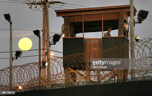 A US Army soldier stands watch in a guard tower as the moon rises over Camp Delta in the Guantanamo Bay detention center on March 29 2010 in...