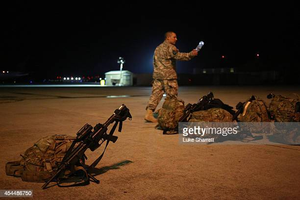 S Army soldier stands watch over gear belonging to members of the US Army's 159th Combat Aviation Brigade 101st Airborne Division during a homecoming...