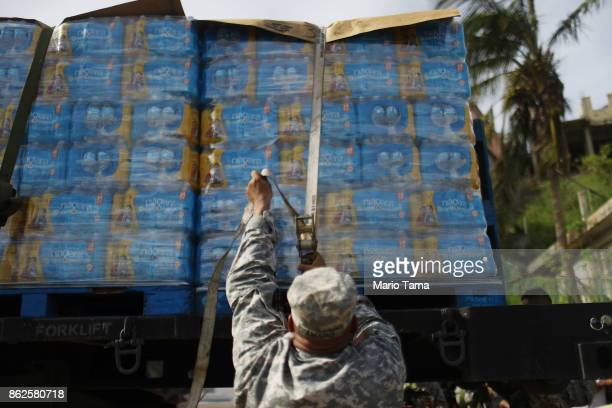 Army soldier starts to unload a shipment of water, provided by FEMA, in a neighborhood without grid electricity or running water on October 17, 2017...