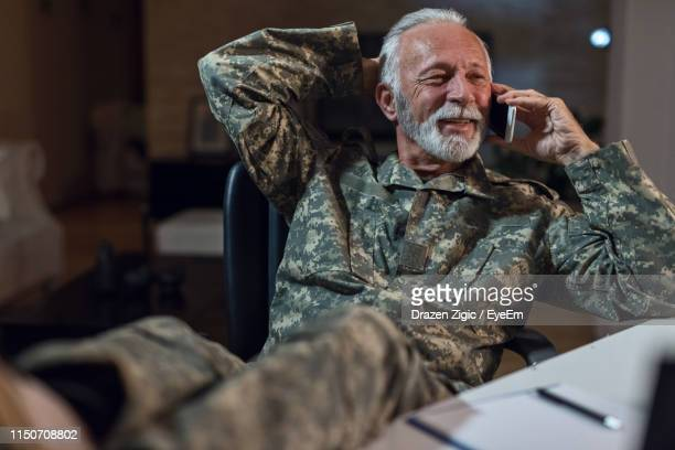army soldier talking over smart phone while sitting on chair - objetivo militar - fotografias e filmes do acervo
