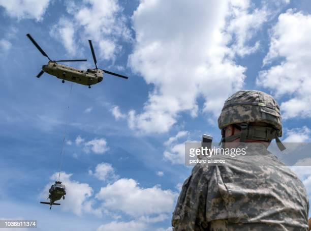 Army soldier uses his smart phone to film the recovery of a Sikorsky UH60 Black Hawk helicopter by a Boeing CH47 Chinook helicopter in Plankenfels...