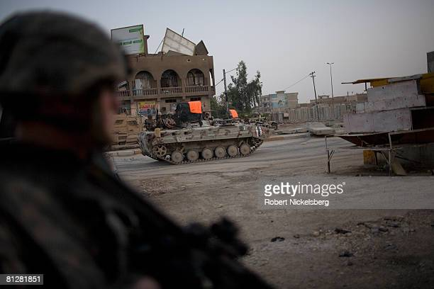 Army soldier watches as Iraqi Army vehicles cross the concrete barrier dividing Sadr City to take control of the 25 million Shia dominated stronghold...