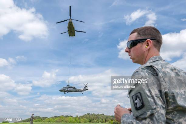 Army soldier watches the recovery of a Sikorsky UH60 Black Hawk helicopter by a Boeing CH47 Chinook helicopter in Plankenfels Germany 18 May 2015 The...
