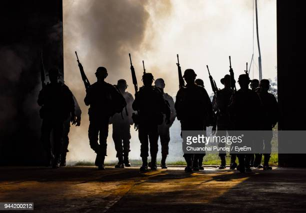 army soldier with rifle walking against sky - riot stock pictures, royalty-free photos & images