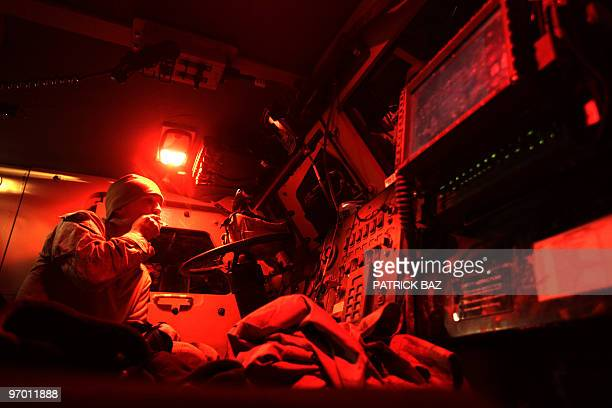 A US army soldier with Task Force Thorn sits in his MRAP at night in Trikh Nawar on the northeastern outskirts of Marjah on February 22 2010 A NATO...