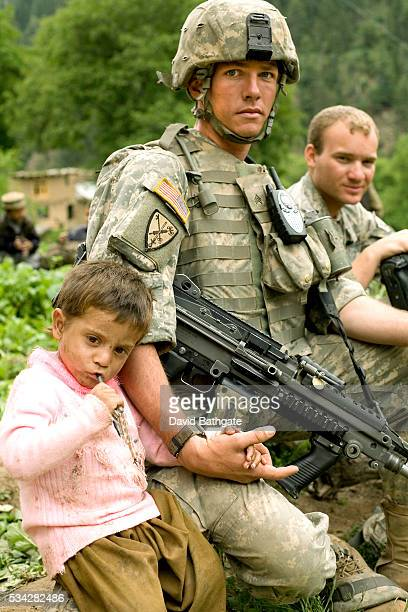 US Army soldier with the 173rd Airborne Division's Provincial Reconstruction Team waits with a young patient to see doctors at a village makeshift...