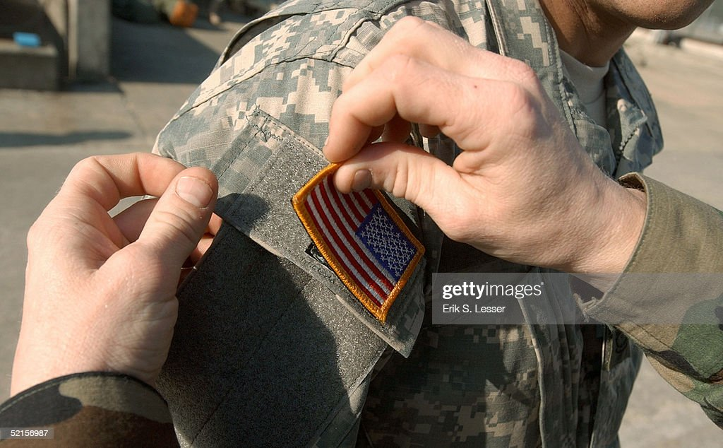 S. Army soldier with the Georgia National Guard's 48th Infantry Brigade has U.S. flag applied with Velcro to his newly issued Army Combat Uniform (ACU) February 8, 2005 at Fort Stewart, Georgia. The ACU includes a new universal camouflage pattern and provides moisture wicking, functionality and ergonomics.