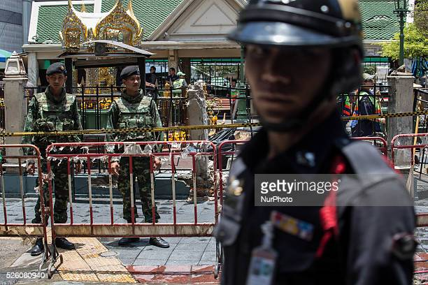 Army soldiers and a policeman stand guard front of the Erawan Shrine, as we can see the damaged on the wall and the barriers caused by the bomb, in...