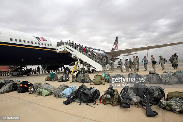 A US army soldiers board a plane as they begin their journey home out of Iraq from the alAsad Air Base west the capital Baghdad on November 1 2011...
