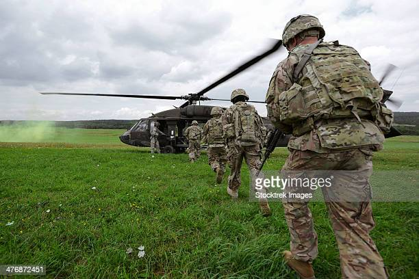 u.s. army soldiers board a uh-60 black hawk helicopter. - military exercise stock pictures, royalty-free photos & images