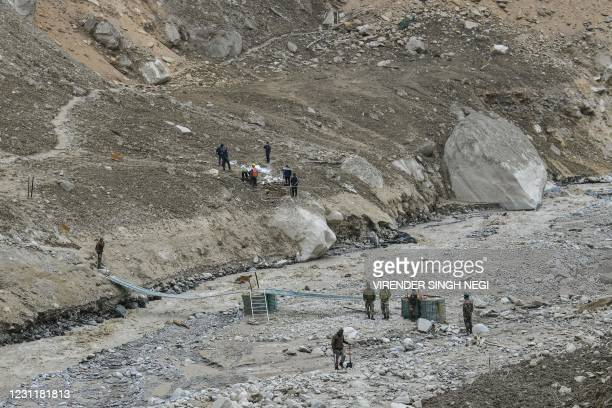 Army soldiers build a temporary bridge for residents near Raini village of Chamoli district on February 15 following a flash flood thought to have...