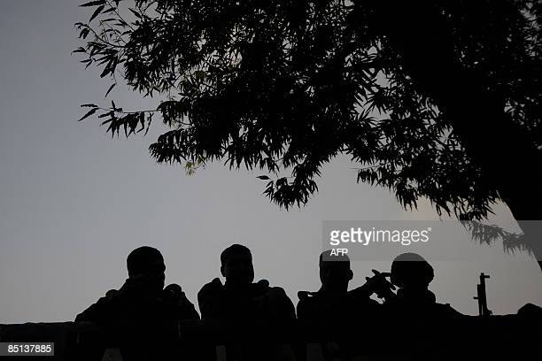 Army soldiers chat near the camp of border security force in Dhaka on February 27 2009 a day after a fierce gun battle broke out inside the...
