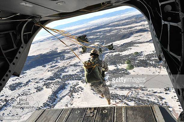 Army Soldiers conduct airborne operations out of a Chinook helicopter as they leap from the Chinook ramp onto the snowy terrain below.