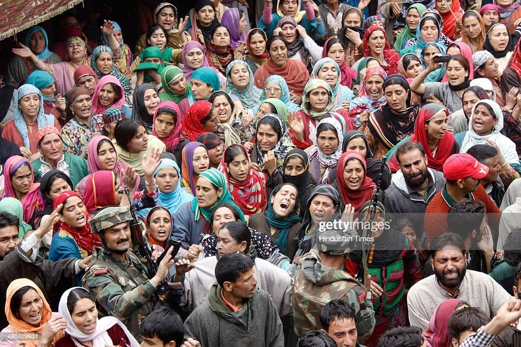 Army soldiers consoling the native villagers during the funeral procession of an Army soldier Mushtaq Ahmad Mir at Qazipora Chadoora district, on May 20, 2014 in Srinagar, India. Mushtaq Ahmad Mir, an Army soldier who was killed in an encounter at Chadoora yesterday. An Army soldier was killed and three others injured in an ongoing encounter at Chadoora in district Budgam of central Kashmir. Sources said that militants managed their escape from the spot and forces were now extending the cordon to more areas.