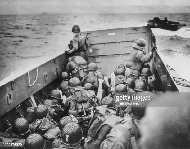 US Army soldiers crouch behind the bulwarks of US Coast Guard landing barges as they cross the English Channel towards the shores of Normandy France...