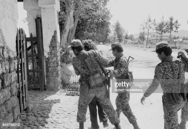 Army soldiers direct a suspected leftist guerrilla into a building for interrogation in the military compound January 1 1982 in Santa Cruz del Quiché...