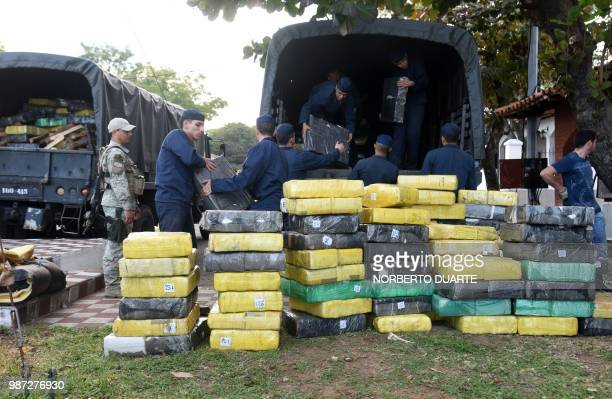 Army soldiers download 14182 kilos of seized marijuana from a truck to be incinerated in Asuncion on June 29 2018 The drug was seized on Moday in...