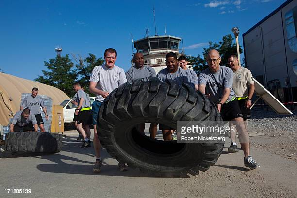 Army soldiers flip a large tractor tire for exercise May 11, 2013 at Bagram Air Base, Afghanistan. U.S. Soldiers and marines are part of the NATO...