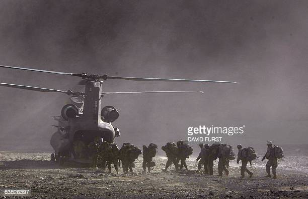 Army soldiers from 2-506 Infantry 101st Airborne Division and Afghan National Policemen and Army load onto a UH-47 Chinook helicopter landing to pick...