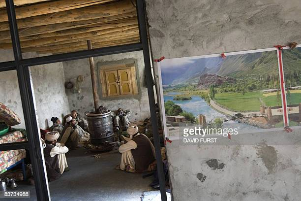 Army soldiers from 2-506 Infantry 101st Airborne Division drink tea with Afghan men in a village while on patrol through the Spira mountains in...