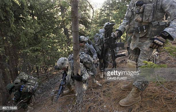 Army soldiers from 2-506 Infantry 101st Airborne Division help a struggling fellow soldier as they climb a mountain to set up a patrol base at it's...