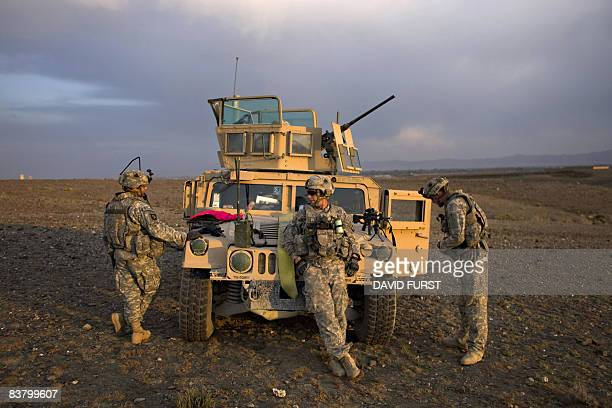 Army soldiers from 2-506 Infantry 101st Airborne Division stand around their humvee during preparations for Operation Shir Pacha into the Derezda...