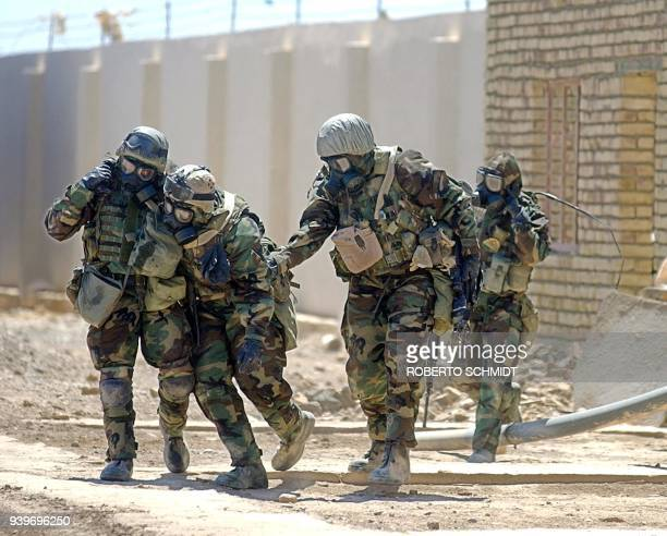 US Army soldiers from 28 Infantry 2nd Brigade 4th Infantry Division wearing their full chemical protection suits assist a comrade overcome by heat as...