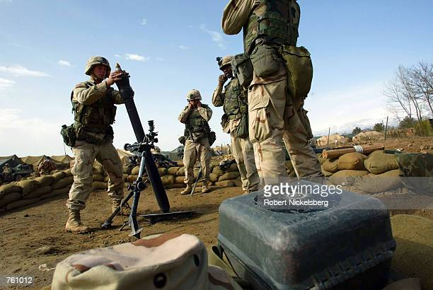 US army soldiers from a 101st Airborne Battalion field artillery team prepare to fire an 81mm mortar round during a sightingin exercise April 7 2002...