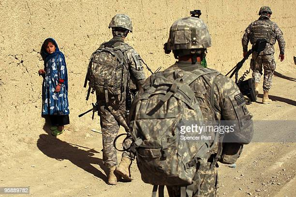 Army soldiers from a Provincial Reconstruction Team walk by a girl on January 20 2010 in Orgune Afghanistan The soldiers from Forward Operating Base...