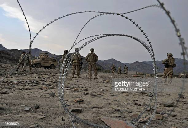 US army soldiers from Alfa battery company HHB 37 Field Artillery Regiment 3rd Bct 25th ID walk across rocky terrain during a mission in the Turkham...