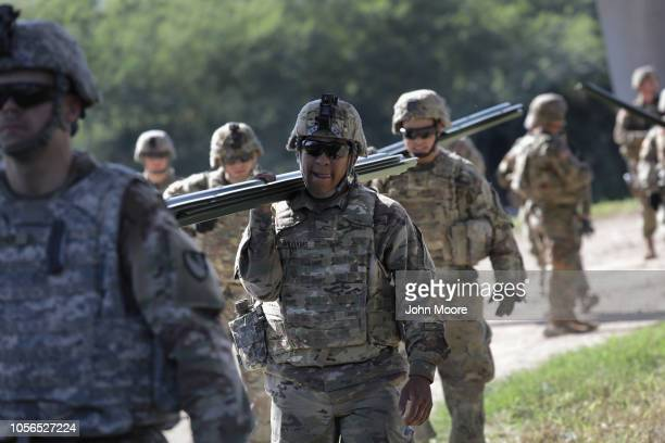 S Army soldiers from Ft Riley Kansas carry fence posts while installing protective wiring along the Rio Grande at the USMexico border on November 2...