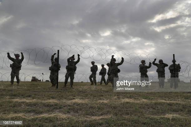 S Army soldiers from Ft Riley Kansas string razor wire around the port of entry at the USMexico border on November 4 2018 in Donna Texas President...