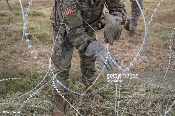 S Army soldiers from Ft Riley Kansas string razor wire near the port of entry at the USMexico border on November 4 2018 in Donna Texas President...