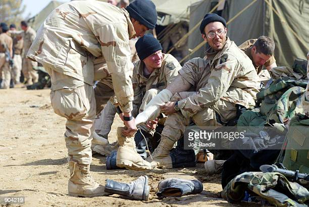 S Army soldiers from the 101st Airborne change their socks and boots March 11 2002 after they returned to Bagram airbase from the fighting in eastern...