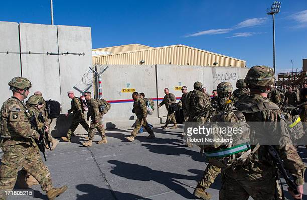 Army soldiers from the 101st Airborne Division, foreground, arrive May 11, 2013 as U.S. Army soldiers depart, background, at Bagram Air Base,...